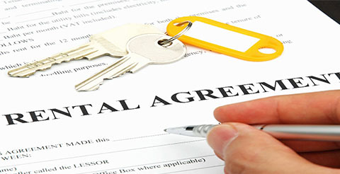 A close up of someone signing a rental agreement.